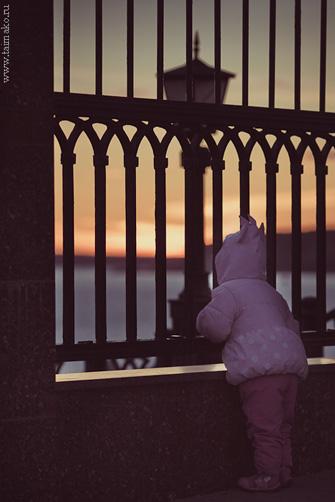 Ребенок, закат и решетка